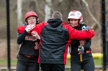 Wamogo head coach Dave Sylvester, center, praises and exhorts his players Samantha Sylvester #3, left, and Savannah Wheeler #20, right, in a big rally, during a Girls BL Softball game between Wamogo and Nonnewag at Nonnewaug High School in Woodbury on Thursday. Bill Shettle Republican-American