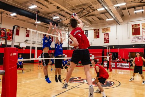 Lewis Mills players Tim Groleau #23, left, and Nick Jennings #25 go up to block the spike of Cheshire's Aiden Godfrey #1, during a boys volleyball match between Lewis Mills and Cheshire at Cheshire High School in Cheshire on Friday. Bill Shettle Republican-American