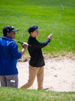 Pomperaug's Zachary Wisnefsky, right, chips out the the sand as Lewis Mills' Jon Ventres, left, look on during the Woodland Individual golf tournament held Thursday at Oxford Greens in Oxford. 20 schools from throughout the state completed in the tournament. Jim Shannon Republican American