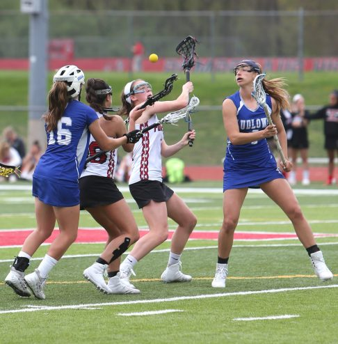 Pomperaug High School's Kathleen Schenk and teammate Camden Frissora battle two defenders for the ball after the faceoff during the girls varsity lacrosse game against Fairfield Ludlowe in Southbury on Saturday afternoon. Emily J. Reynolds. Republican-American