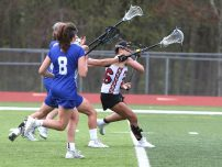 Pomperaug High School's Camden Frissora battles three defenders on her way up the field during the girls varsity lacrosse game against Fairfield Ludlowe in Southbury on Saturday afternoon. Emily J. Reynolds. Republican-American