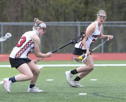 Pomperaug High School's Avery Lenczewski, left, passes the ball to teammate Madeline Mickune during the girls varsity lacrosse game against Fairfield Ludlowe in Southbury on Saturday afternoon. Emily J. Reynolds. Republican-American