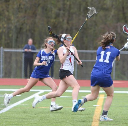 Pomperaug High School's Kathleen Schenk battles two defenders on her way up the field during the girls varsity lacrosse game against Fairfield Ludlowe in Southbury on Saturday afternoon. Emily J. Reynolds. Republican-American