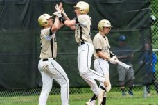 Woodland's Colby Linnell #14 walks up to the plate, right, as Woodland's Alex Kalentek #16, center, celebrates with his teammate Woodland's Mike Szturma #2, left, after both scoring runs, during the CIAC 2019 State Baseball Tournament Class M Quarterfinals between Lewis Mills and Woodland at Woodland Regional High School in Beacon Falls on Thursday. Bill Shettle Republican-American