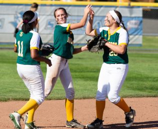 Holy Cross' Allie Brown (1) is congratulated by teammates Brianna Greenlaw (11) and Valerie Nobrega (25) after making a diving catch during their Class S semi-final game with Coginchaug Monday at West Haven High School. Jim Shannon Republican American