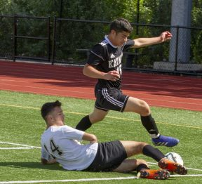 Kaynor Tech #15 Carlos Lara leaps over the legs of WCA Spartans #14 Eric Ozen as he kicks the ball out of bounds during play at the Waterbury Soccer Jamboree Saturday morning at Crosby. Jonathan Wilcox Republican-American