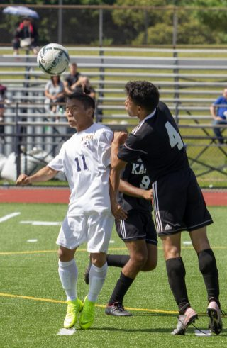 Kennedy #11 Sher Fh Htoo heads the ball away from Kaynor Tech #4 Juan Rojas during the Waterbury Soccer Jamboree Saturday morning at Crosby. Jonathan Wilcox Republican-American