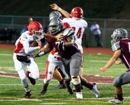 Wolcott's Matt Stoeckert (18) tries to fight off a tackle by Naugatuck's Herve Tshibamba (77) during their season opening game Friday at Naugatuck High School. Jim Shannon Republican-American