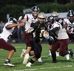 Woodland's Jason Palmieri (8) scrambles for yardage as Torrington's Benjamin Brooks (44) and his defense swarms in during NVL football action at Woodland High School Friday night. Michael Kabelka / Republican-American