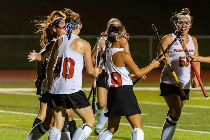Pomperaug teammates Jessica Evans (40), left, and Leah Kowalasky (56), right, clack sticks with Meili Dipietro (29), center after she scored a goal, during a SWC girls field hockey game between Joel Barlow and Pomperaug at Pomperaug High School on Wednesday. Bill Shettle Republican-American
