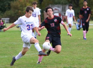 #33 Brett Davino of Nonnewaug High kicks a ball past #12 Zachary Kelly of Wamogo High during soccer action in Litchfield Monday. Steven Valenti Republican-American