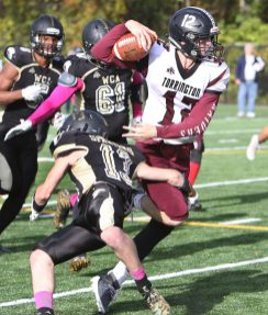 #12 Conrad Avallone of Torrington High tries to break away from #13 Josh Ross Jr. of Waterbury Career Academy while making a run up the field during football action in Waterbury Thursday. Steven Valenti Republican-American