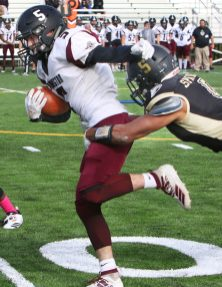 #5 Jacob. Coleman of Torrington High gets wrapped up by #5 Jalen Gopie of Waterbury Career Academy while running during football action in Waterbury Thursday. Steven Valenti Republican-American