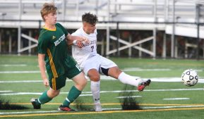 #7 Lucas Silva of Naugatuck High takes a shot on goal past #15 Colin Harrigan of Holy Cross High during NVL Soccer action in Waterbury Monday. Steven Valenti Republican-American