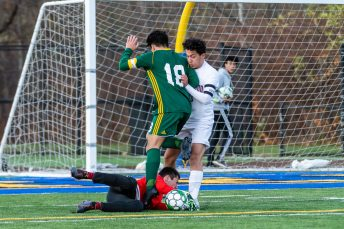 Holy Cross goalkeeper Aidan Nixon (0) lays on the ground after making a save on the ball in traffic with his teammate Luke Zipoli (18) and Torrington's Xavier Rodas (10), battling above, during the quarterfinals of the Boys NVL Soccer Tournament between Torrington and Holy Cross at Municipal Stadium on Saturday. Bill Shettle Republican-American