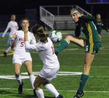 #16 Alyssa Hebb of Holy Cross High clears a ball past #19 Morgan Matyoka and #5 Jenna Tracey of Wolcott High during the NVL soccer tournament semifinals at Municipal Stadium in Waterbury Monday. Steven Valenti Republican-American
