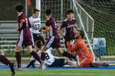Naugatuck goalkeeper David Green (31), right, makes a save in front of the sliding Woodland's Cole Barrows (8), during the NVL Boys Soccer final between Naugatuck and Woodland at Municipal Stadium on Thursday. Naugatuck beat Woodland 2-1. Bill Shettle Republican-American