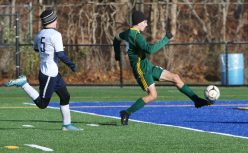 #7 Brian Silva of Holy Cross High scores a goal as #5 Andrew Fiano of Bolton High defends in second round of Class S boys soccer tournament at Municipal Stadium in Waterbury Wednesday. Steven Valenti Republican-American