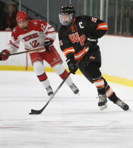 #15 Sean Dunfee of Watertown-Pomperaug looks to pass while being pursued by #12 Aiden Gaudet of Cheshire during hockey action in Middletown Saturday. Steven Valenti Republican-American