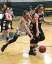 Holy Cross High School's Alyssa Hebb battles Woodland High School's Kylie Bulinski during the girls varsity basketball game at Holy Cross on Monday night. Emily J. Tilley. Republican-American