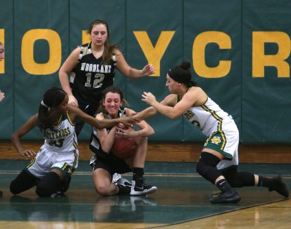 Woodland High School's Ava DeLucia battles Holy Cross High School's Cayla Howard and Jenna Mowad for a loose ball during the girls varsity basketball game at Holy Cross on Monday night. Emily J. Tilley. Republican-American