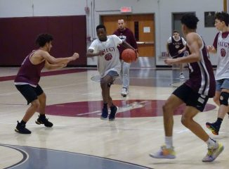 Naugatuck sophomore Ese Onakpoma pushes the pace under the watchful eye of coach Mike Wilson during practice last Friday. (Kevin Roberts/RA)