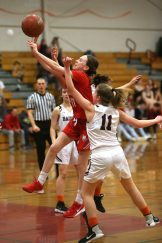 Wolcott High School's Amanda Sullivan goes up for a shot over Torrington High School's Suzie Navin during the girls varsity basketball game on Thursday night, Feb. 13, 2020. Emily J. Tilley. Republican-American
