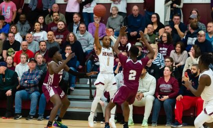 Sacred Heart's Lorenzo Washington passes off the ball while being defended by Naugatuck's Keywan Garris (3) and Ese Onakpoma (2) during their key NVL match-up Friday at Alumni Hall at Sacred Heart High School. Jim Shannon Republican-American