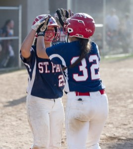 St. Paul's Katrina Roy (20) and Lindsey O'Bright (32) celebrate after coming in to score on a bases loaded double by teammate Katelynn Oullette during their NVL softball semi-final game against Watertown Thursday at Naugatuck High School. Jim Shannon Republican American