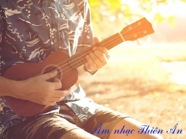 Cách cầm đàn ukulele khi ngồi.
