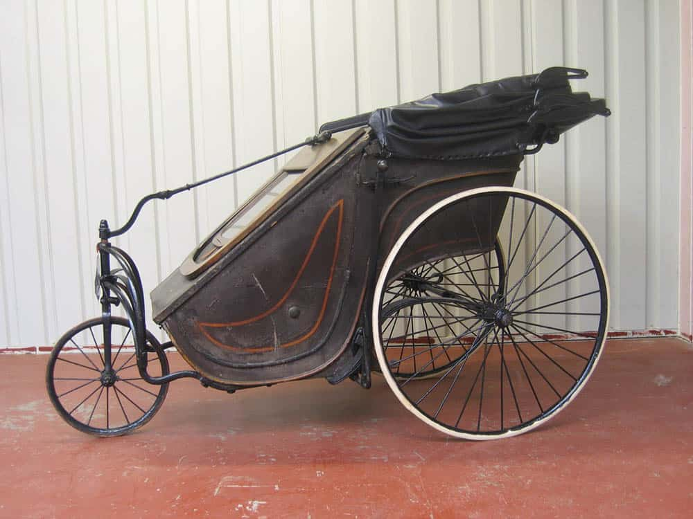 An antique wheelchair from generations' passed, made with leather and thin wheels