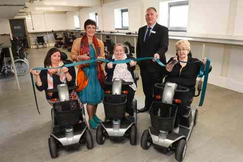 The Centre opens their Livingston Mobility Service where manual wheelchairs and scooters are available to loan for visitors to The Centre. Pictured cutting the ribbon is Angela Constance with Patrick Robbertze (Director, The Centre) and visitors to The Centre who will be making use of the scooters (left to right) Morven Pritchard, Mary Couper and Carol Seivewright
