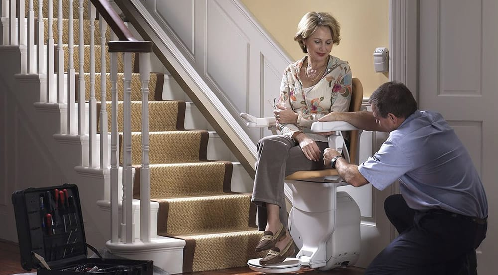 Stairlift being fitted by an engineer in a woman's home
