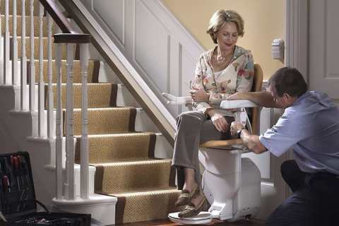 Stairlift being fitted by an engineer in a woman
