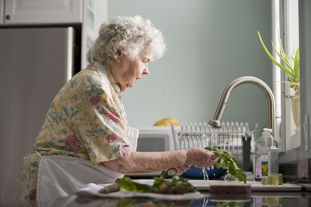 elderly woman at home washing up