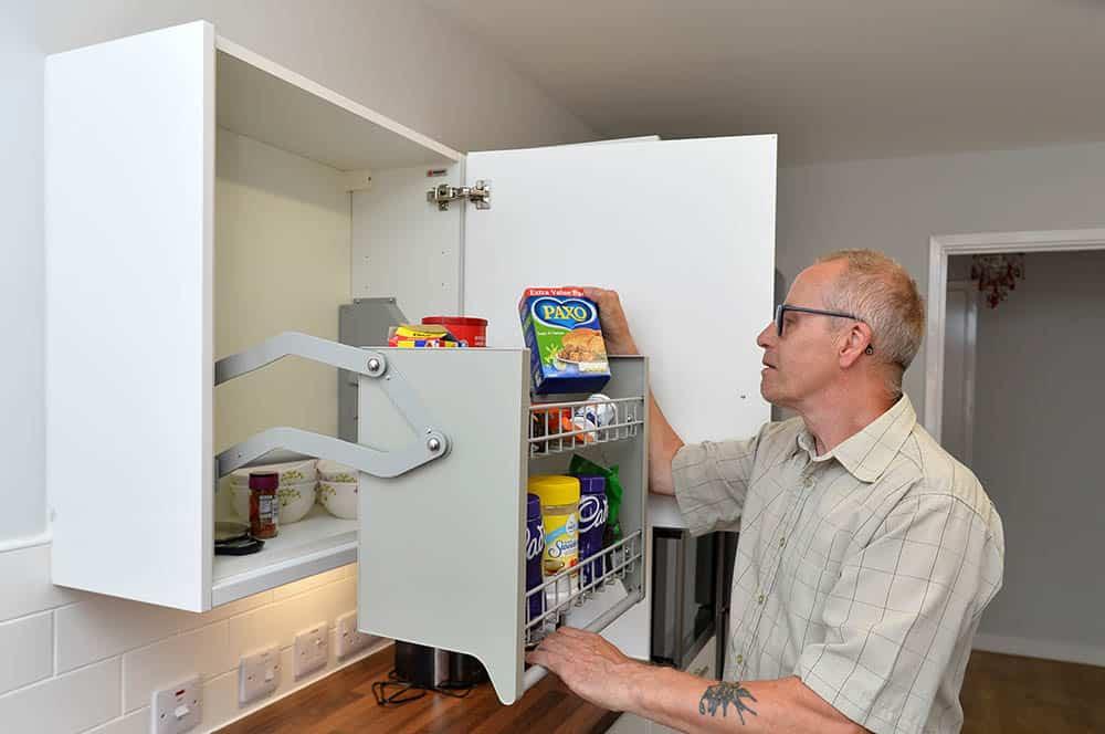 Habinteg Housing Association Rawcliffe Grove Hull. Resident Geoffrey Bone using adapted cupboard in the kitchen.