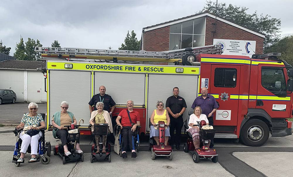 Pride Mobility scooter user group in front of fire truck in Bicester with Shire Mobility
