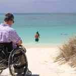 Wheelchair user at a sandy beach image