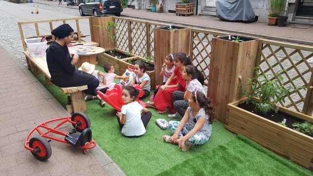 Kinderen op een parklet luisteren naar een verhaal