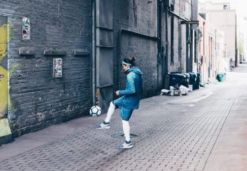 Voetballende jongere op straat