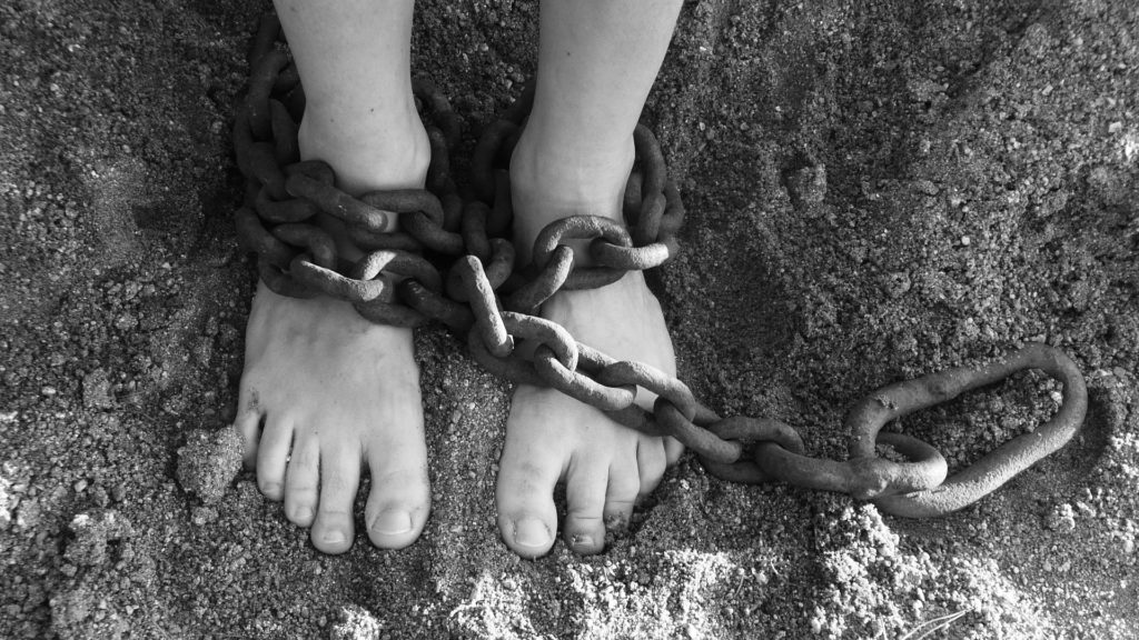 chains on ankles in sand