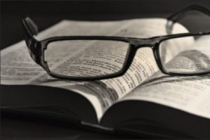 bible with thick-framed eyeglasses lying atop