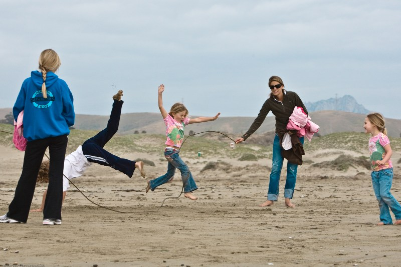 Kids play on Morro Strand State Beach by skiping rope which actually is a giant kelp strand