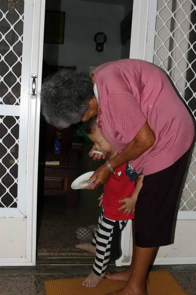 孫子兩腳跨在戶碇兩旁,阿嬤用七夕粿擦嘴幫助收涎