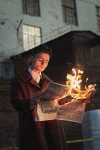 man reading burning newspaper