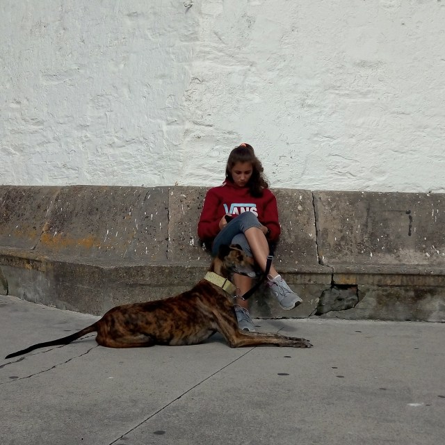 A girl relaxes with her dog in Luarca