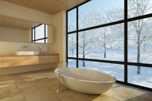 Free standing white bath in warm stone clad architect designed interior with black framed window looking out onto snowy sunlit garden typical of architects design value in macclesfield by Mark Burgess