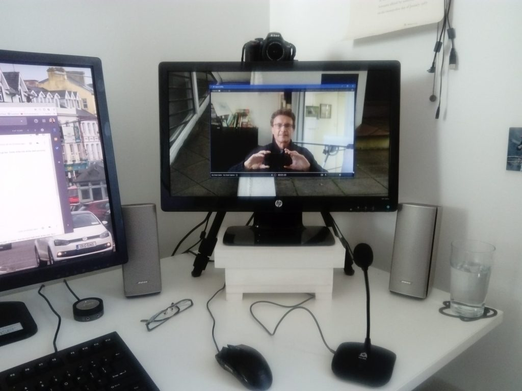 A PC work station showing screen,  Nikon D3300 DSLR digital camera as webcam on try pod and the desktop furniture.