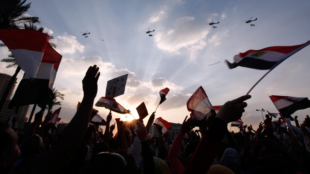 Military Helicopters fly over the square with huge Egyptian flags hanging below them