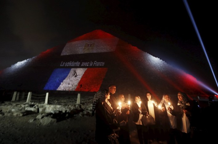 "Egyptians light candles as the French and Egyptian flags and France's national colours of blue, white and red are projected onto one of the Giza pyramids, in tribute to the victims of the Paris attacks, on the outskirts of Cairo, Egypt, November 15, 2015. The words on the pyramid read: ""Solidarity with France""."